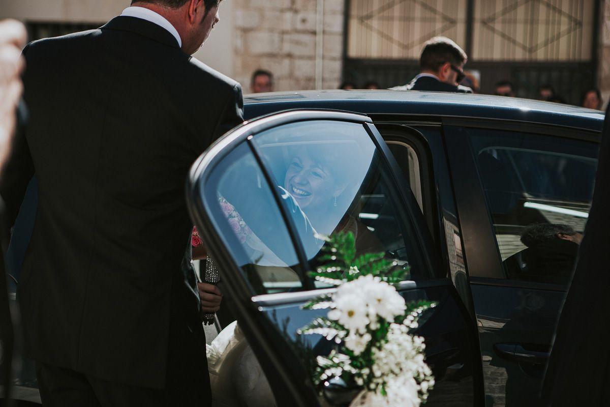 novia sonriendo al salir del coche antes de casarse - fotógrafo bodas valladolid
