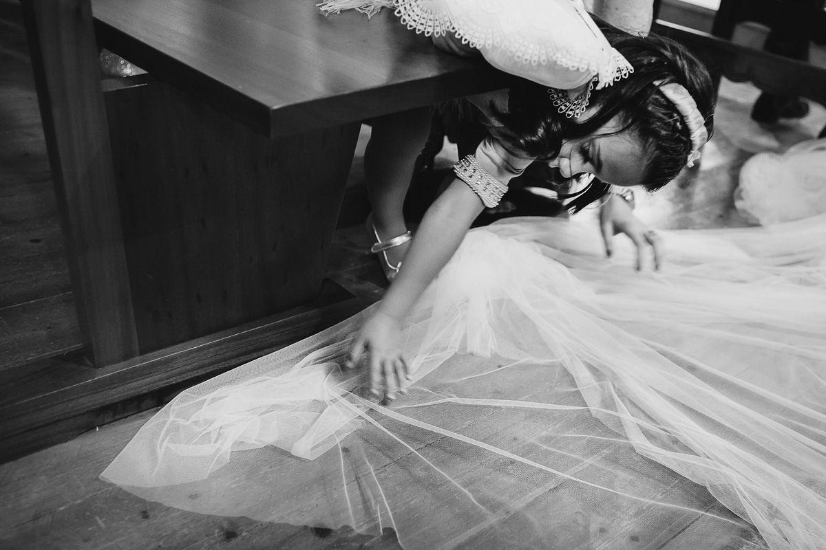 Detalle niña colocando el vestido de la novia - fotógrafo de bodas en Valladolid