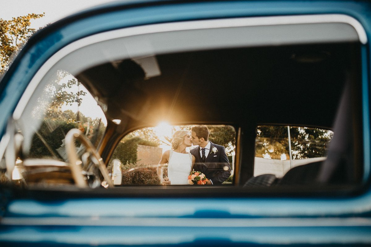 Pareja besándose en coche vintage el día de su boda en Palencia.