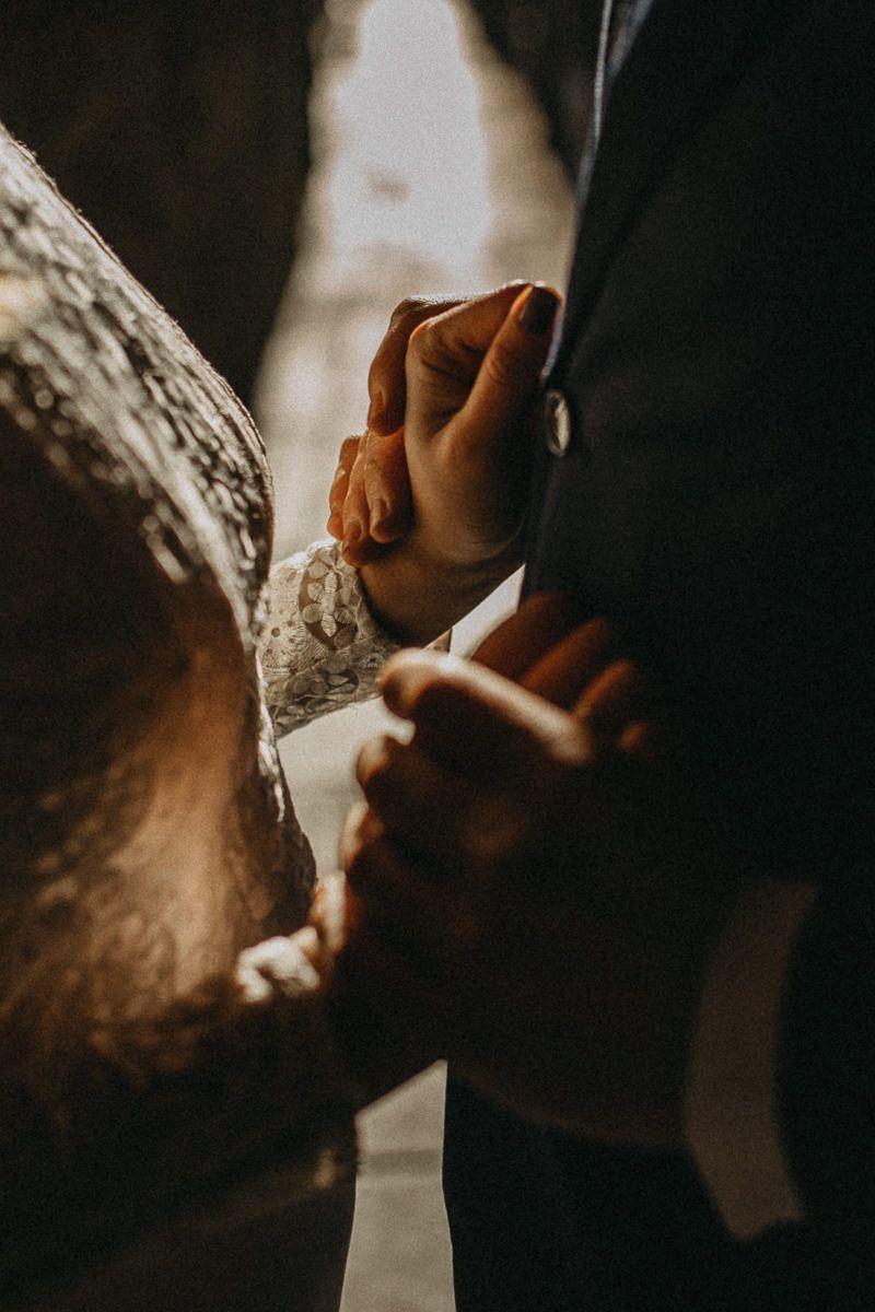 Fotografía delicada del detalle de unas manos cogidas en una sesión de postboda